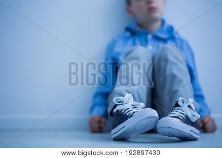 Sad boy sitting on a floor in a room