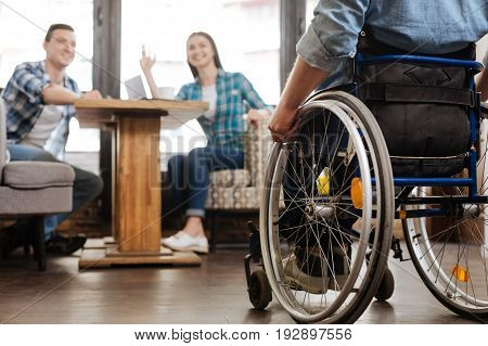 Disability is not a problem. Easygoing creative inspiring man joining his friends in a cafe who inviting him helping their new business project