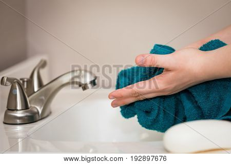 Someone drying their hands with a blue towel after washing them