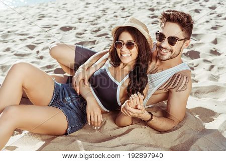 Happy Young Couple Relaxing On Beach Together On Summer Day