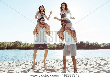 Happy Friends Piggybacking And Enjoying Summertime While Spending Time On Beach