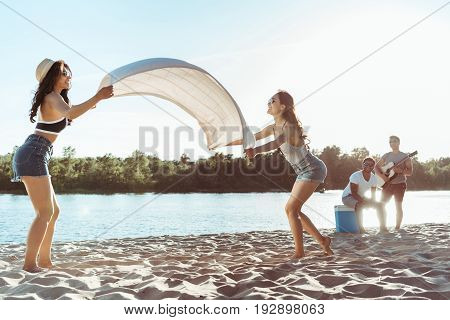attractive girls waving beach blanket on sandy riverside at daytime