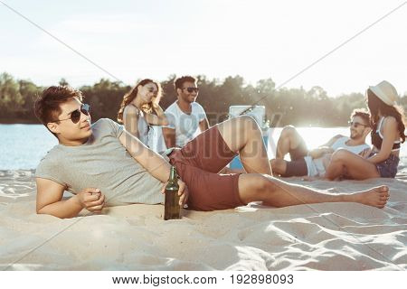 Young Man Lying On Sandy Beach While Her Friends Resting Behind On Riverside