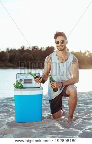 young smiling man taking beer from portable fridge on sandy beach