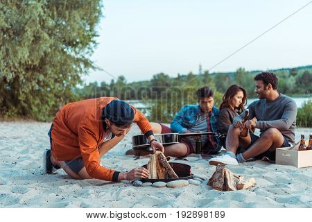 friends trying to make a bonfire while spending time on sandy beach