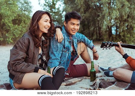 young smiling asian couple sitting on sandy beach and listening their friend playing guitar