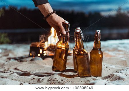 Human Hand Taking Bottle Of Beer From Sand With Campfire Behind