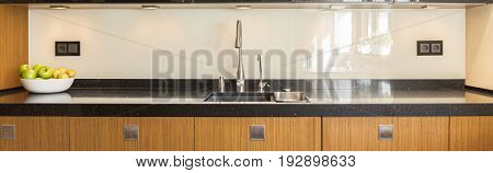 Kitchen interior with wooden furniture and marble worktop