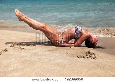 Caucasian woman practicing yoga at seashore on Cyprus
