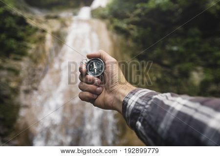 Man Explorer Searching Direction With Compass On Waterfall Background Point Of View Hiking Journey Travel Trek Concept