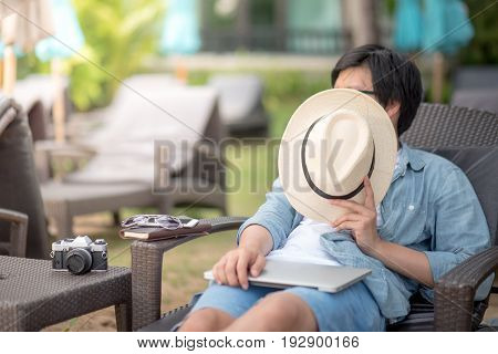 Young Asian man lying on bench near the beach with laptop notebook and camera for outdoor working digital nomad lifestyle concepts
