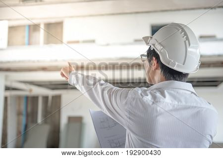 Engineer or Architect checking architectural drawing while wearing a personal protective equipment safety helmet at construction site. Engineering Architecture and building construction concepts
