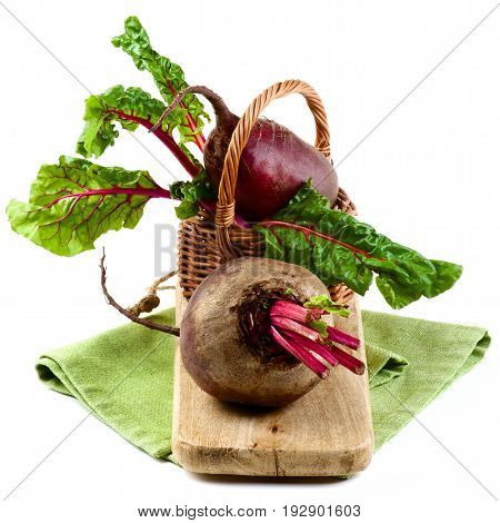 Two Fresh Raw Organic Beet Roots with Green Beet Tops in Wicker Basket on Wooden Board and Napkin isolated on White background