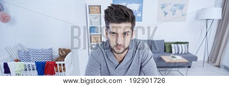 Single man in living room overworked by home duties