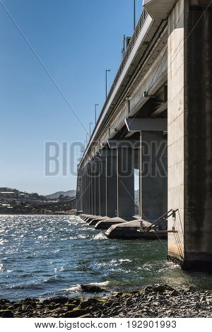 Hobart Australia - March 19. 2017: Tasmania. Shot along the succession of pillars of the long high Tasman Highway Bridge over Derwent River seen from base on beach. Blue sky choppy water shoreline
