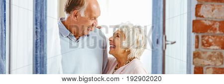 Happy senior couple smiling at each other and standing next to the window