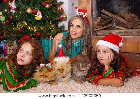 Two beautiful smiling litle girls wearing a christmas clothes, hugging her cats, the curly girl with a red tie in her hair while the brunette girl is wearing a christmas hat with her mom looking somewhere laying on a white carpet.