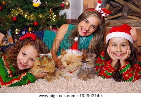 Beautiful family wearing a christmas clothes, hugging her cats, the curly girl with a red tie in her hair while the brunette girl is wearing a christmas hat next to her mom, laying on a white carpet, with a christmas tree background.