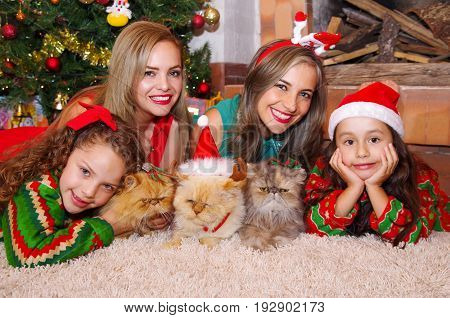 Two beautiful moms with her little girls, wearing a christmas clothes, the curly girl with a red tie in her hair while the brunette girl is wearing a christmas hat posing both hands in her cheek, both families lying on white carpet in a christmas tree bac