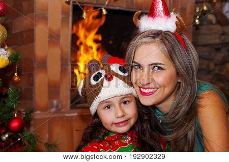 Happy mother and daugher at christmas, litle girl wearing a deer hat and mom a christmas hat, with an indoor chimmey background.