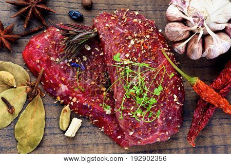 Two Marinated Raw Boneless Beef Steaks with Herbs and Spices Garlic and Chili Pepper closeup on Wooden Cutting Board. Top View