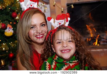 Happy mother and smiling daugher at christmas, litle girl wearing a deer hat and mom a christmas hat, with an indoor chimmey background.