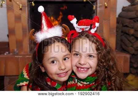 Close up of two beautiful smiling litle girls wearing a christmas clothes laying on a white carpet, with a indoor chimmey background.