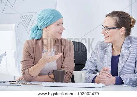 Young patient with a blue headscarf talking to her doctor