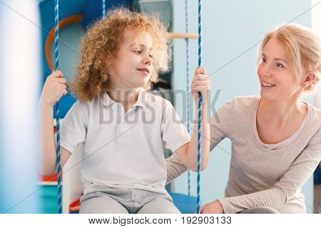 Boy sitting on a swing and talking to physiotherapist