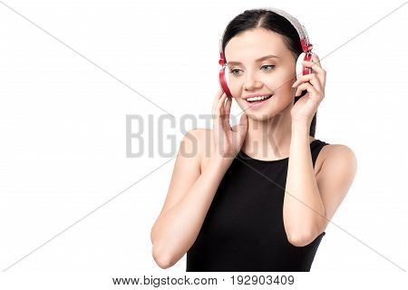 Smiling Young Woman Listening Music In Headphones Isolated On White