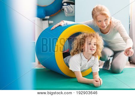 Professional therapist explaining new exercise to a little boy