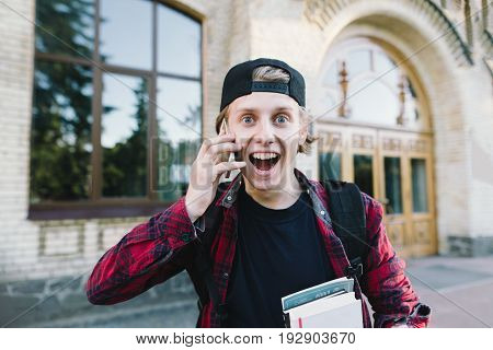 A funny and very emotional young man speaks by phone on the background of architecture. Amazed student in a shirt and cap speaks by telephone on the background of the university.