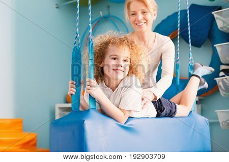 Happy boy laying on therapy swing and his therapist holding him