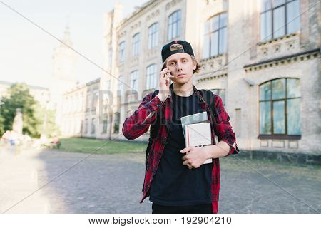 A student with a serious look and books in his hand spreads on a mobile phone on the background of the university building. A look at the camera. Student Concept.
