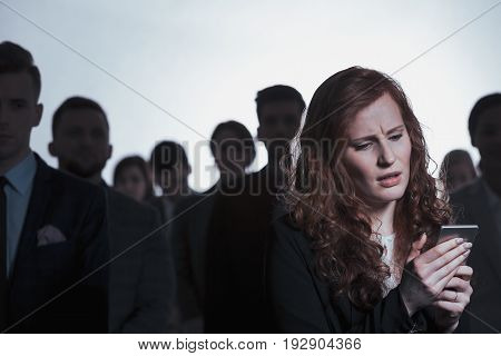 Woman using mobile phone anonymous crowd in background