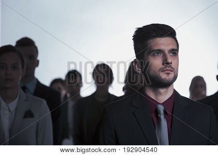 Serious man standing in anonymous crowd of people