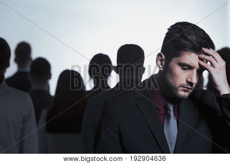 Tired man standing in anonymous crowd of people