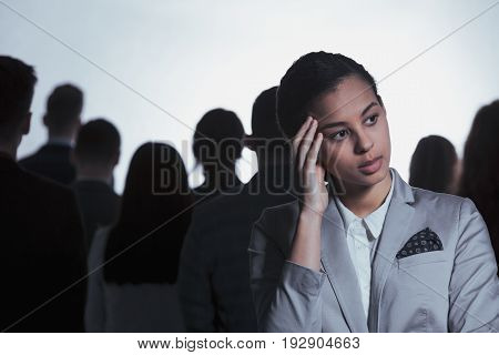 Tired businesswoman having headache standing in anonymous crowd