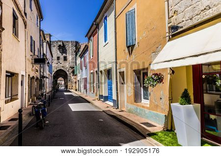 Narrow street with colorful houses and bicycle at Aigues-Mortes southern France