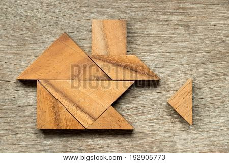 Wooden tangram puzzle in home shape wait for completion (Concept for family building or dream life)