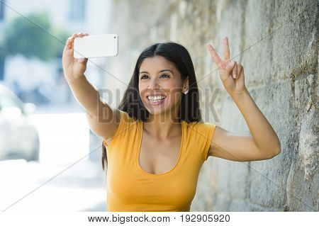 Attractive And Sweet Latin Woman Smiling Happy Taking Self Portrait Selfie Photo With Mobile Phone