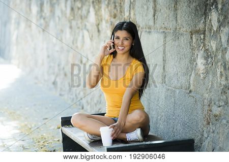 Happy Young Latin Woman Talking And Texting On Smart Phone
