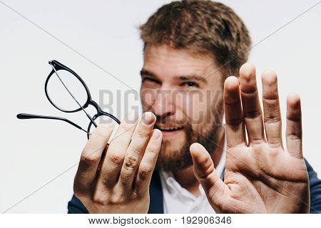 Businessman with a beard on white isolated background holds glasses, portrait.