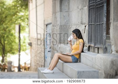Young Attractive Latin Woman In Trendy Casual Clothes Studying Or Working On Laptop Computer
