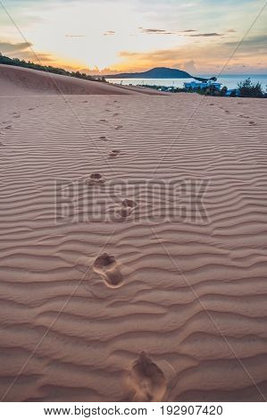 Footprints In The Sand In The Red Desert At Sunrise