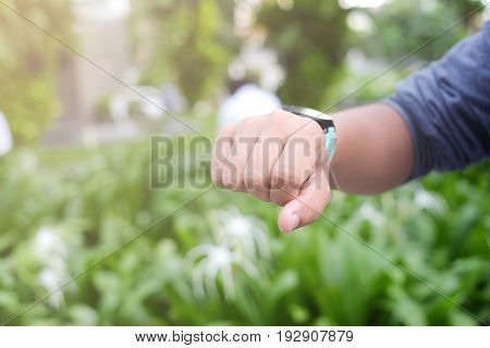 close up man hand with watch for check time or heart rate while resting at park,runner athlete concept