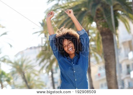 Happy Woman With Arms Outstretched By Palm Trees