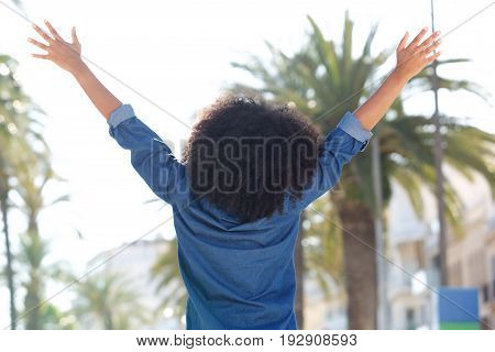 Behind Of Carefree Woman Standing Outside With Arms Outstretched