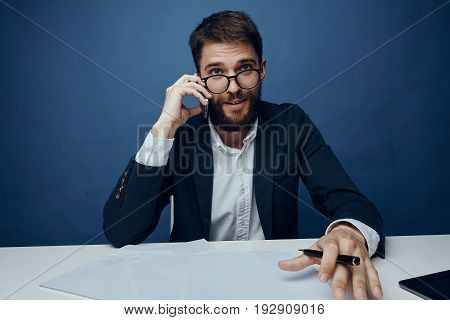 Businessman with a beard in glasses at a desk in the office.