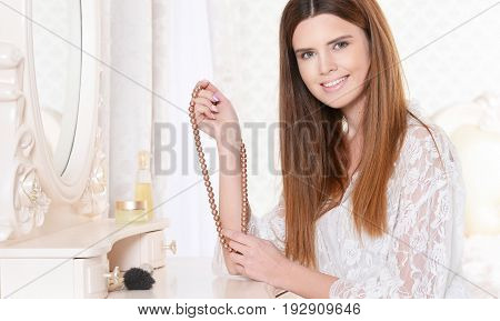 Beautiful young woman sitting at dressing table with necklace of pearls